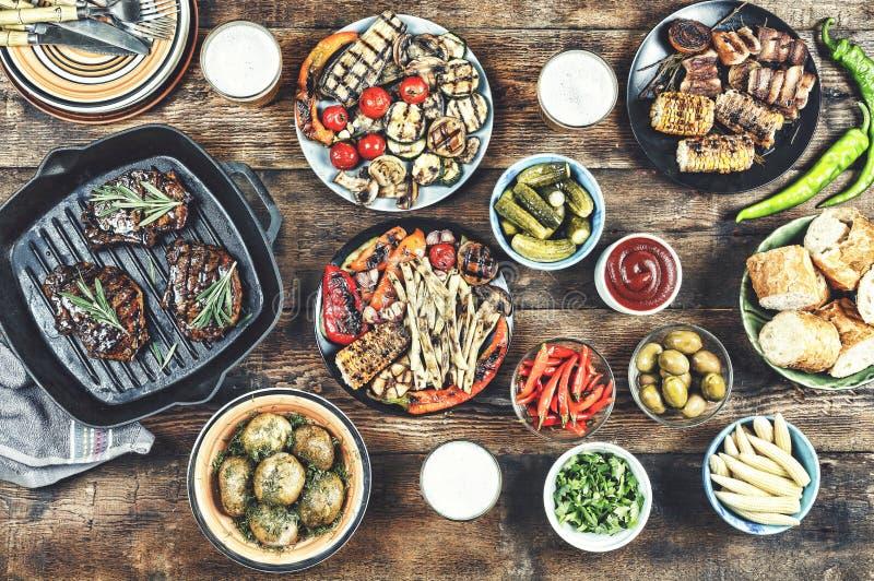 BBQ galler, matställetabell, köttgaller, nya potatisar, sallader, ligh royaltyfria bilder