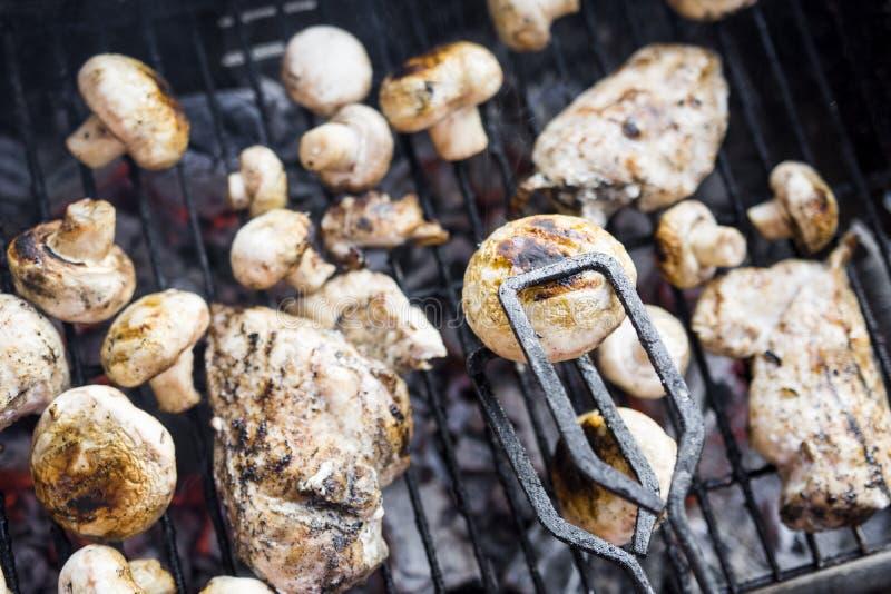 Bbq-galler med många champinjoner och smakligt kött för fegt bröst arkivfoton