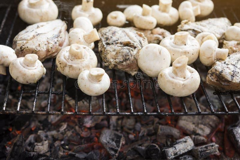 Bbq-galler med många champinjoner och smakligt kött för fegt bröst arkivfoto