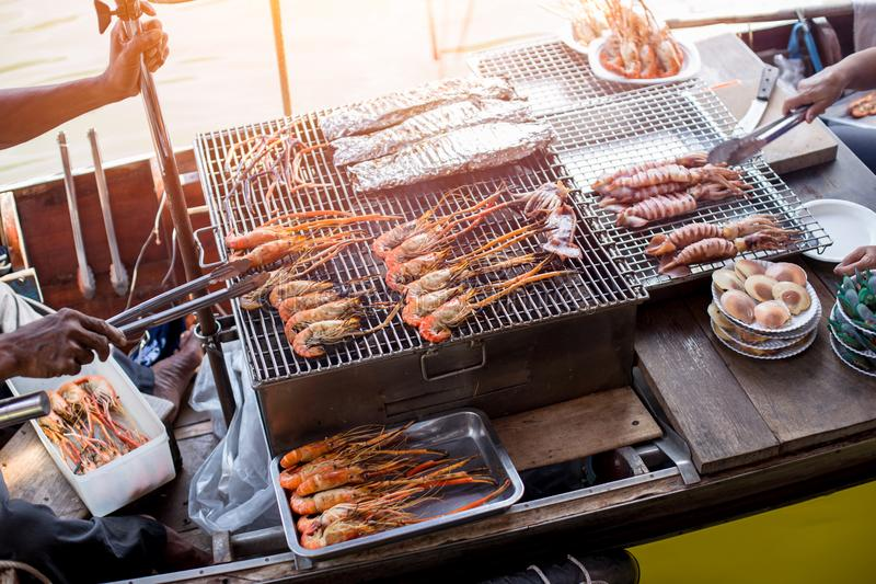 BBQ grill seafood on boat at Amphawa river market. In Thailand stock image