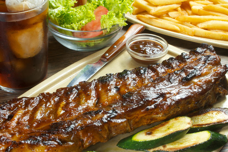 Bbq grilled ribs. Tasty bbq ribs with fries and salad dinner royalty free stock images