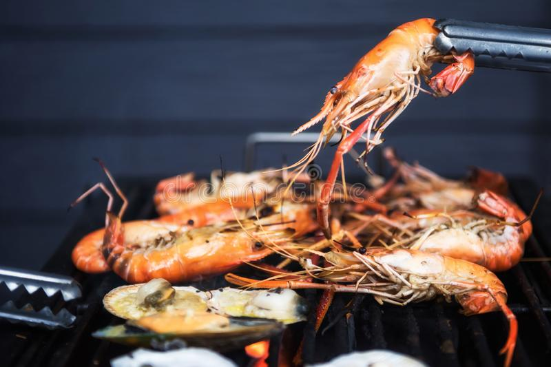 BBQ Grilled shrimps on flaming grill. Grilled shrimps, BBQ or Barbe que seafood on flaming grill with fire burning by coal. Family outdoor party at night, animal stock images