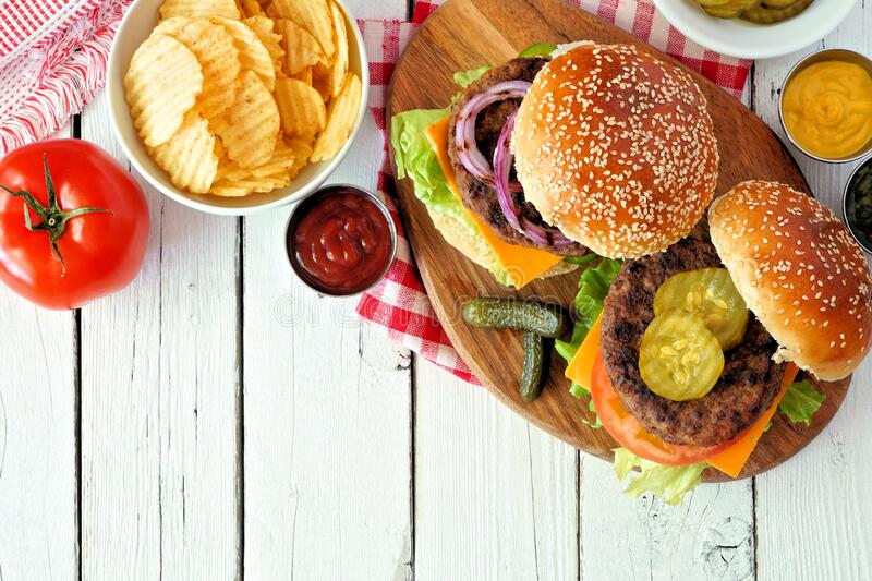 BBQ hamburgers with potato chips, overhead view table scene on white wood stock photo