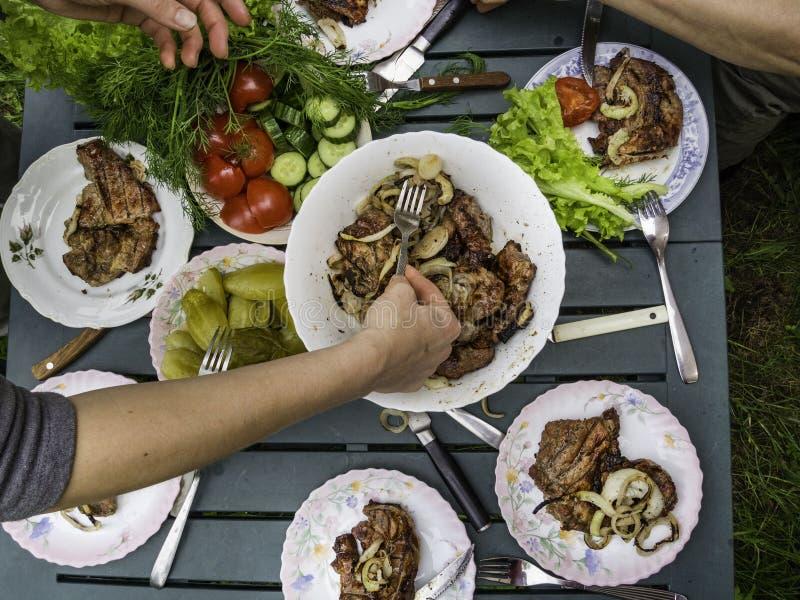 Bbq-kött på landstabellen Familjpicknicktid, den utomhus- bästa sikten för matställepartiet, lägenhet lägger arkivbilder