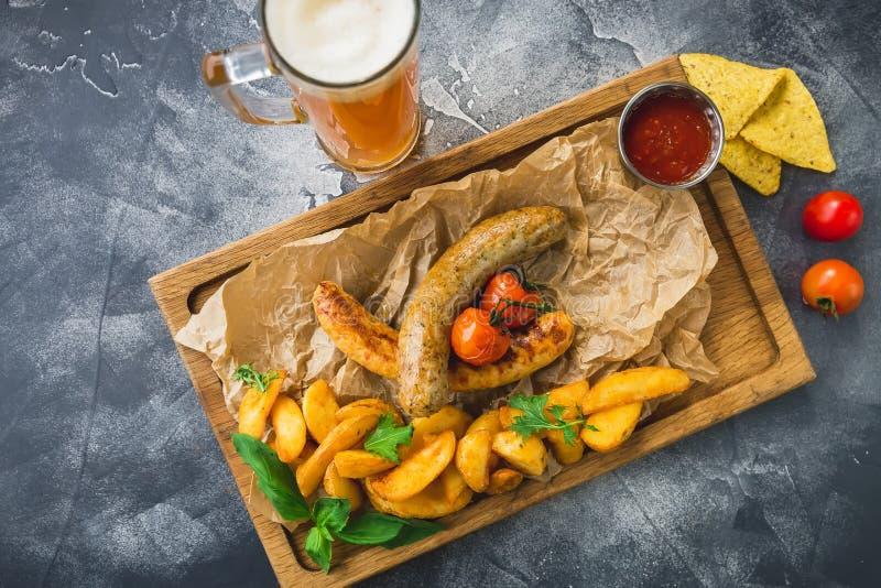 BBQ kiełbasy z smażyć grulami, kiszonym pomidorem na drewnianym talerzu i szkłem alkoholiczny piwo, zdjęcie royalty free