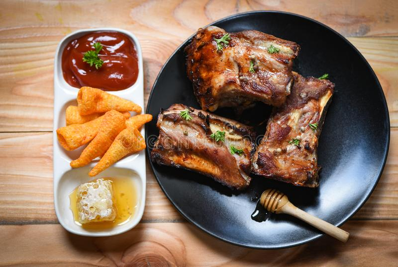 Bbq pork ribs grilled with honey sweet sauce and herbs spices served on the table - Roasted barbecue pork spare rib sliced royalty free stock photo