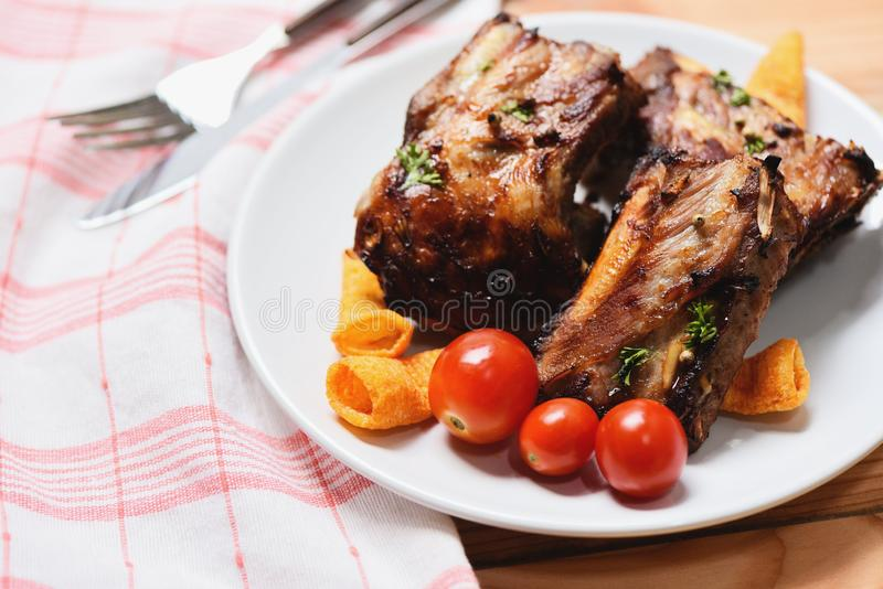 Bbq pork ribs grilled with tomatoes herbs and spices on plate served on wooden table - Roasted barbecue pork spare rib sliced stock image