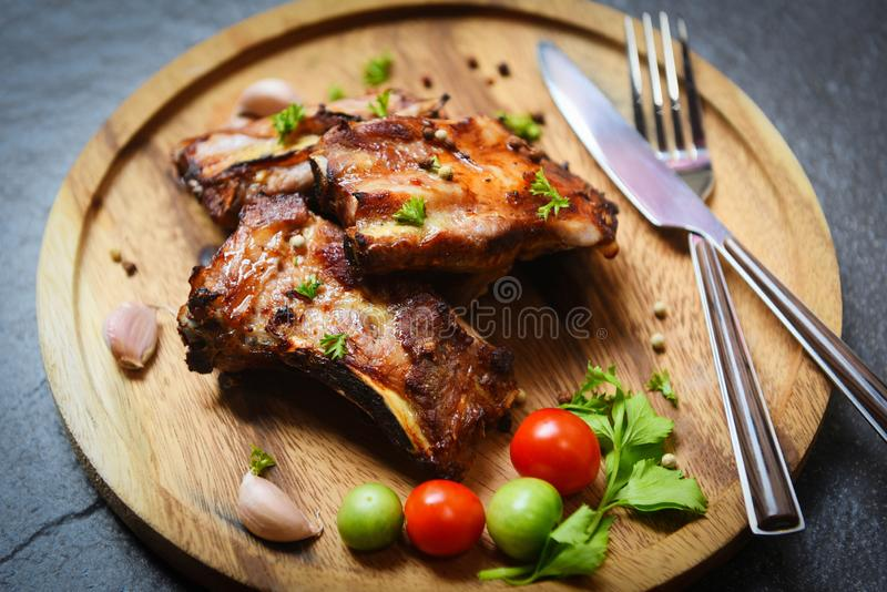 Bbq pork ribs grilled with tomatoes herbs and spices on wooden plate - Roasted barbecue pork spare rib sliced royalty free stock photography