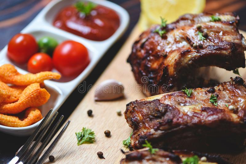 Bbq pork ribs grilled with tomatoes ketchup and herbs spices served on the table - Roasted barbecue pork spare rib sliced stock photography