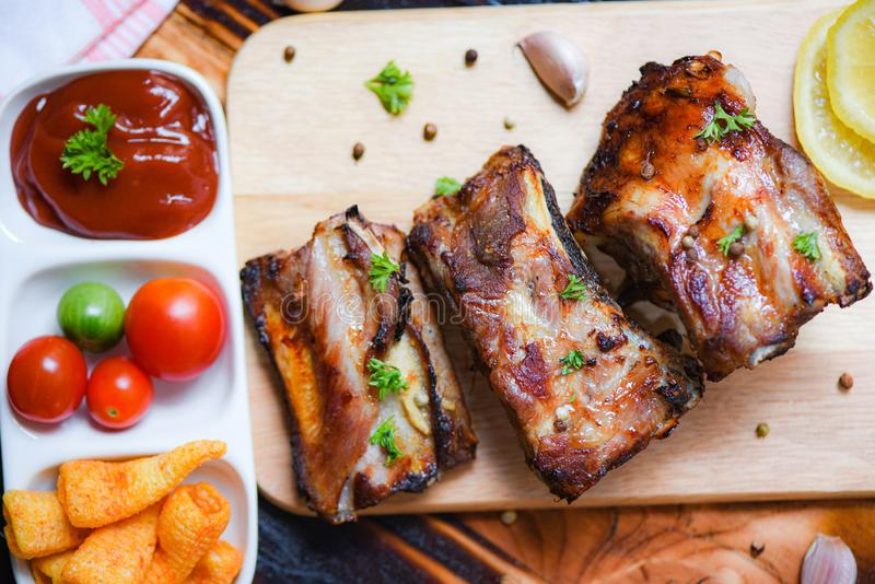 Bbq pork ribs grilled with tomatoes ketchup and herbs spices served on the wooden cutting board on table - Roasted barbecue pork stock images