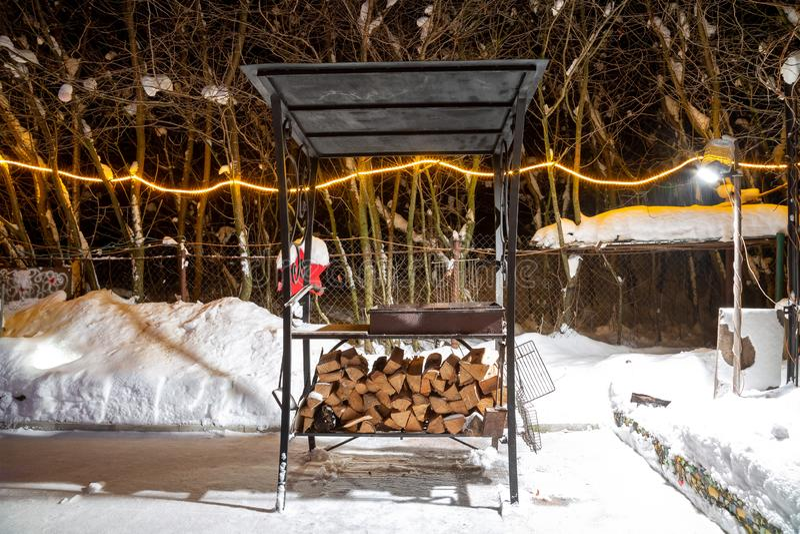 BBQ près de la maison pendant l'hiver La nuit, guirlandes brûlent, il neige Préparation pour la viande de torréfaction Ils s'éten photo libre de droits