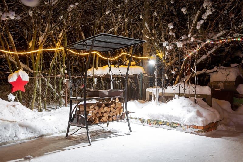 BBQ près de la maison pendant l'hiver La nuit, guirlandes brûlent, il neige Préparation pour la viande de torréfaction Ils s'éten photo stock