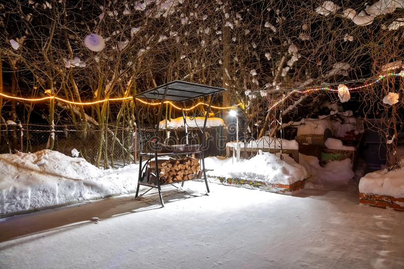 BBQ près de la maison pendant l'hiver La nuit, guirlandes brûlent, il neige Terrain de jeu vide Ils étendent le bois de chauffage photo stock