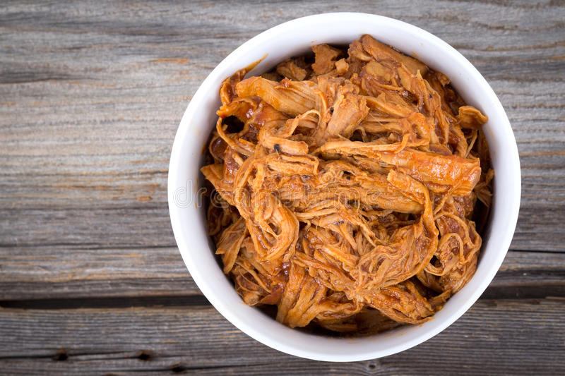 Bbq pulled pork bowl. Over a wooden plank table stock image