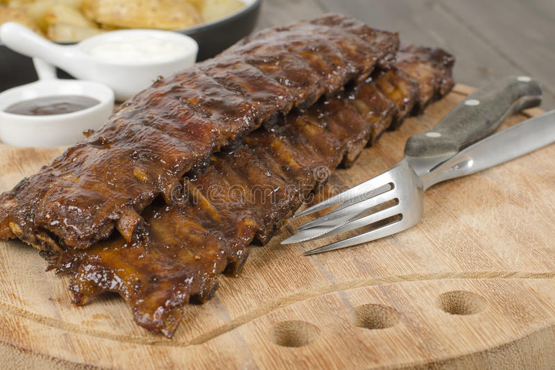 BBQ Ribs. Marinated pork ribs with barbeque sauce dip stock image