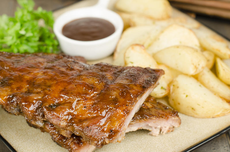 BBQ Ribs. Marinated pork ribs with barbeque dipping sauce and potato wedges with sour cream dip royalty free stock photo