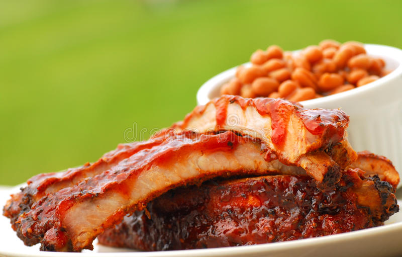 BBQ Ribs and beans. Freshly grilled BBQ Ribs and beans in an outdoor setting royalty free stock images