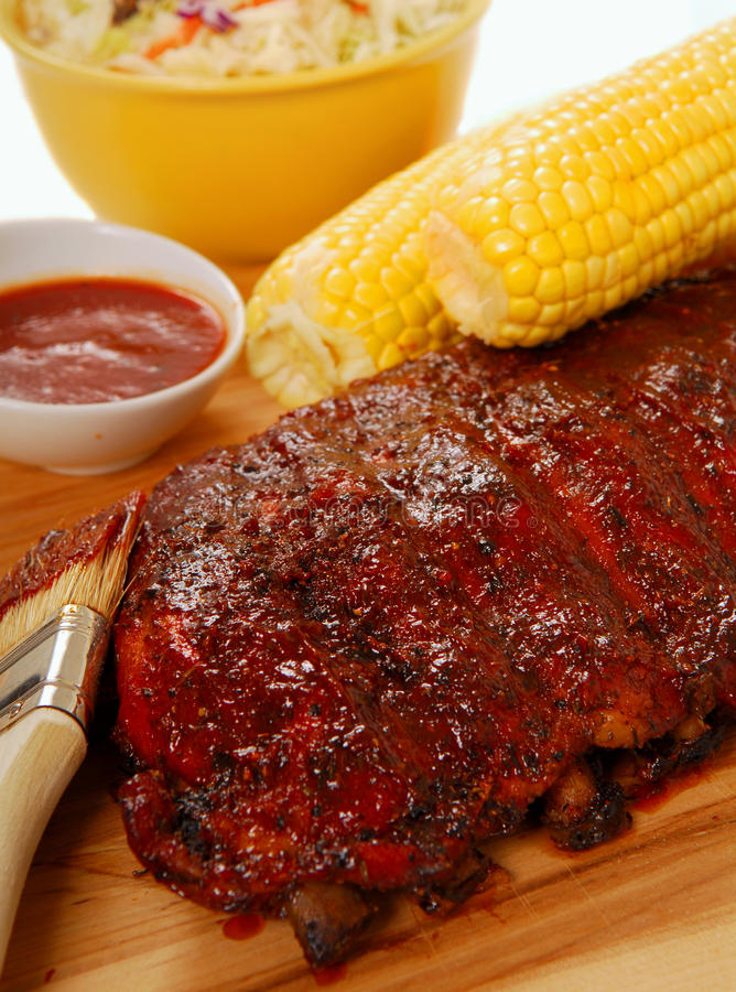 BBQ Ribs with cole slaw, corn and dipping sauce. Freshly grilled BBQ spare ribs with cole slaw, corn on the cob and dipping sauce stock photo