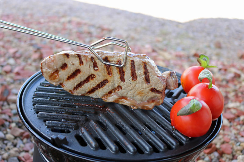 Steak and tomatoes cooking on bbq stock image