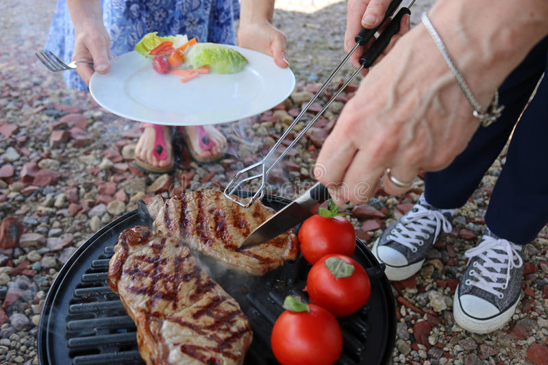 BBQ steak being served. Barbequed beef steak just about to be served on to a plate with salad from a gas barbecue. Tomatoes add colour
