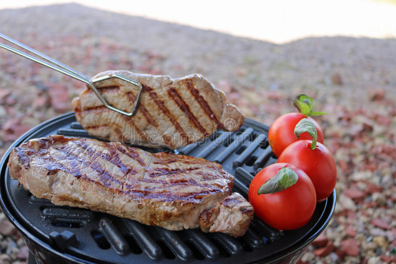 Steak and tomatoes cooking on bbq stock photo