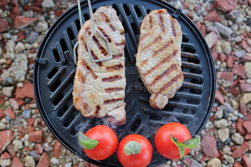 Steak and tomatoes cooking on bbq stock photography