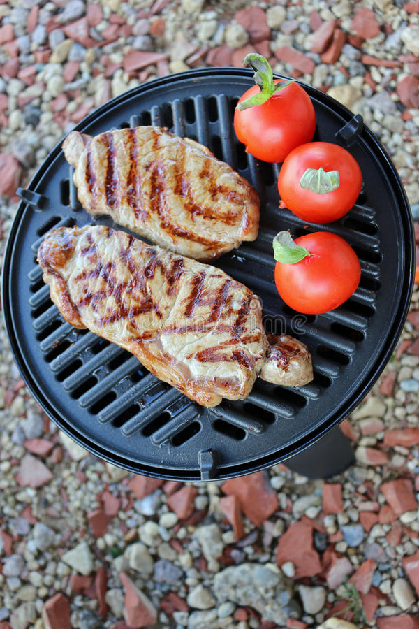 Steak and tomatoes cooking on bbq stock photos