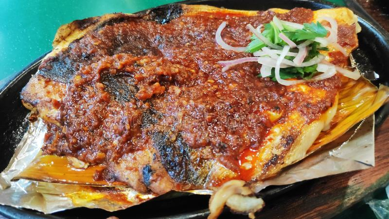 BBQ stingray on a plate. BBQ stingray with spring onions and red chillies paste on a plate stock photo