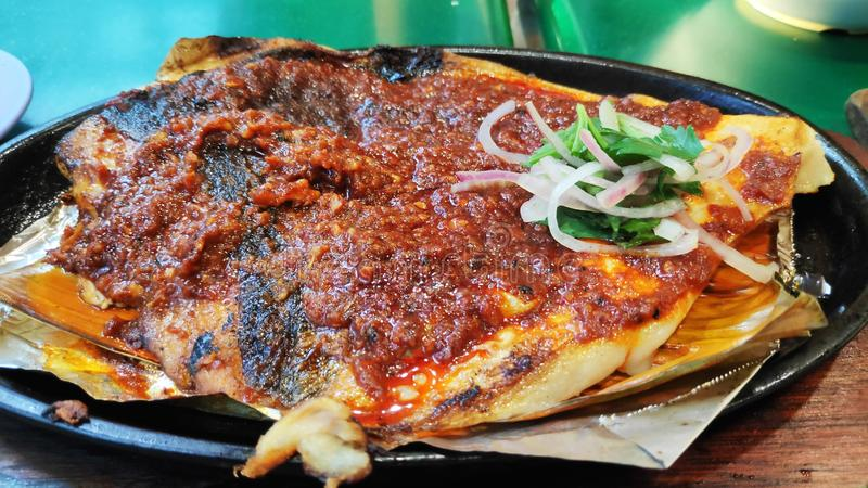 BBQ stingray on a plate. BBQ stingray with spring onions and red chillies paste on a plate royalty free stock photo