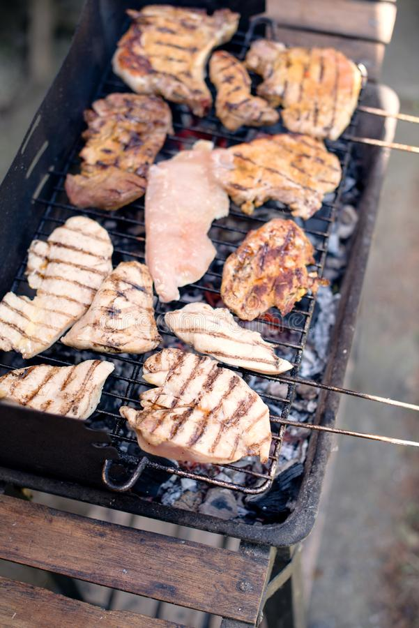 Various cooking meats on a flame grill. BBQ on summer day, meats on a flame grill stock photography