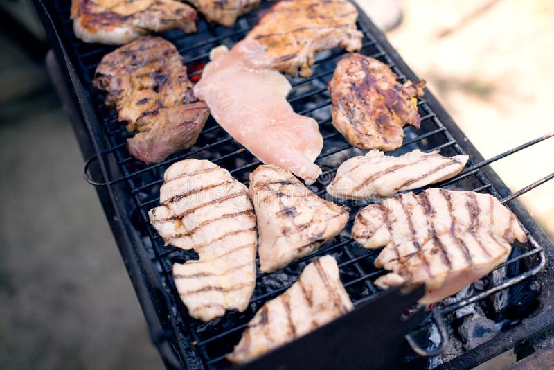 Various cooking meats on a flame grill. BBQ on summer day, meats on a flame grill royalty free stock photos