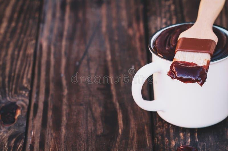 BBQ Szczotkuje z kumberlandem na poradzie nad Nieociosanym Drewnianym tło stołem fotografia royalty free