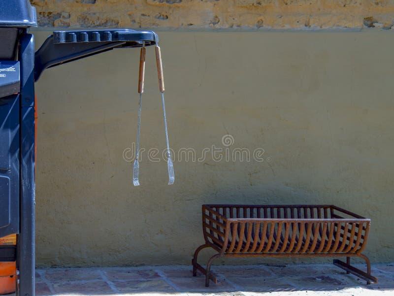 Bbq-tång som hänger från ett BBQ-galler arkivfoto