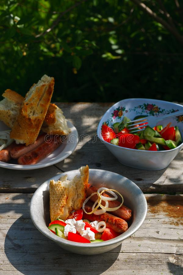 BBQ. Village lunch. grilled sausages with vegetable salad, onion and grilled bread. stock photos