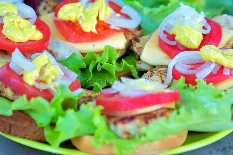 Bbq vlees met kaas, tomaten, uien en sla Op een broodje royalty-vrije stock foto