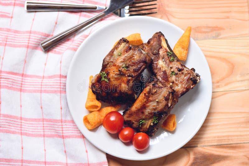 Bbq wieprzowiny ziobro piec na grillu z pomidor pikantność na talerzu i ziele słuzyć na drewnianym stole - Piec grill wieprzowiny fotografia stock