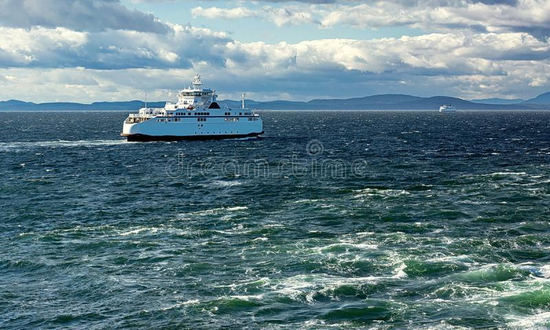 BC Ferry in Strait of Georgia. The ferry makes a regular flight from Vancouver to Nanaimo, windy day, stormy sky, stormy sea, blue water with a green tint royalty free stock photography