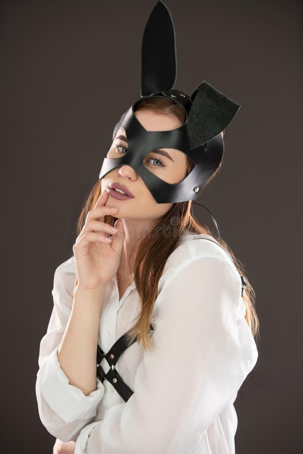 bdsm皮革面具和传送带视图的性感的妇女 库存图片