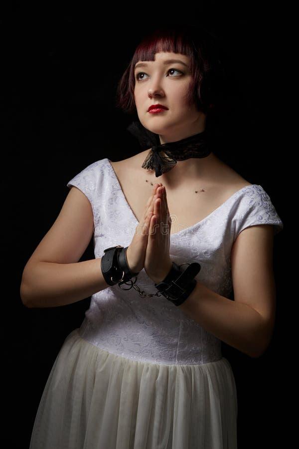 BDSM Menina bonita com mãos na pose da oração fotografia de stock royalty free