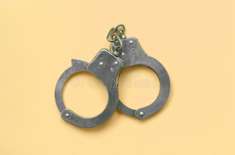 Bdsm and sex games concept. Handcuffs on beige background stock image