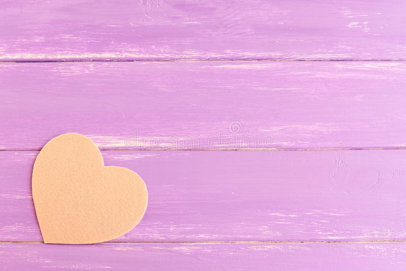 Beż czuł serce na purpurowym drewnianym tle z puste miejsce kopii przestrzenią dla teksta obrazy stock