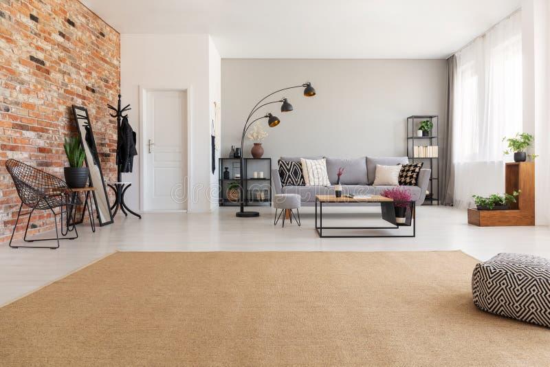Beżowy dywan w nowożytnym żywym izbowym wnętrzu z popielatą leżanką, przemysłowa czarna metal lampa, drewniany stolik do kawy zdjęcie stock
