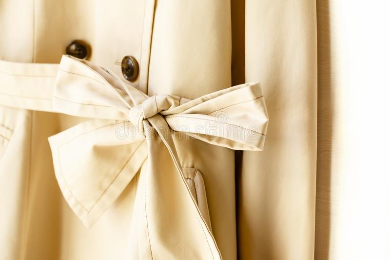 Beżowy elegancki okopu żakiet z faborkiem nad bielem zdjęcie stock