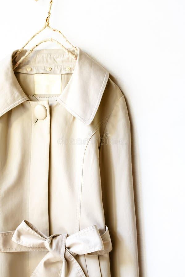 Beżu lub greige okopu elegancki żakiet z faborkiem nad bielem obraz royalty free