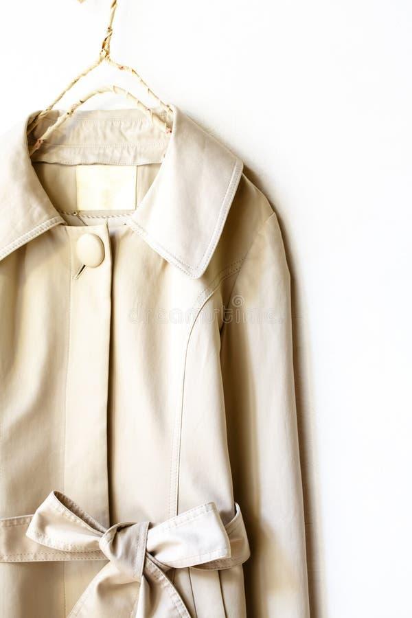 Beżu lub greige okopu elegancki żakiet z faborkiem odizolowywającym nad bielem zdjęcia stock