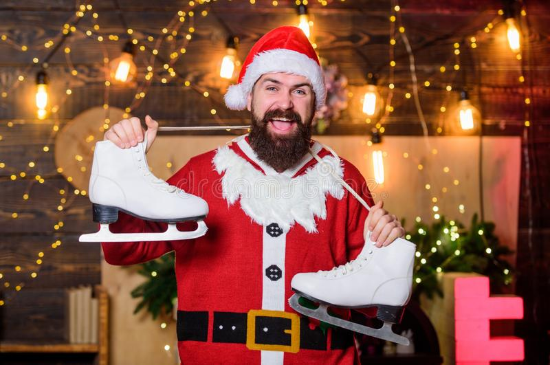 Be active. Snowfall and frost. Santa Claus hold figure skates. Bearded man with pair of skates. Skater christmas gift royalty free stock photos