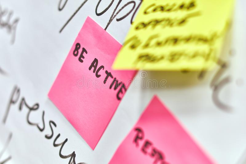 Be active written on pink and yellow paper stickers attached to a flip chart royalty free stock photo