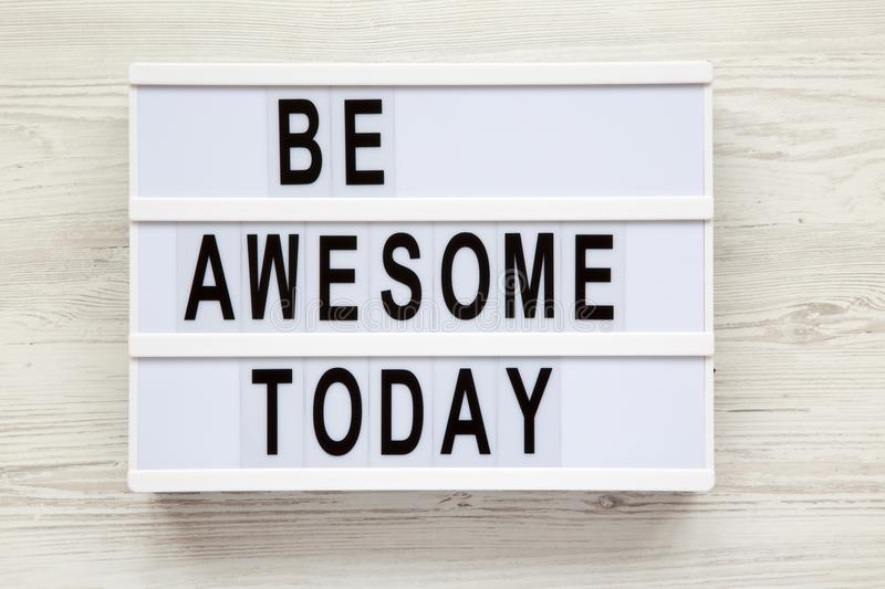 `Be awesome today` word on lightbox over white wooden background, from above. stock image