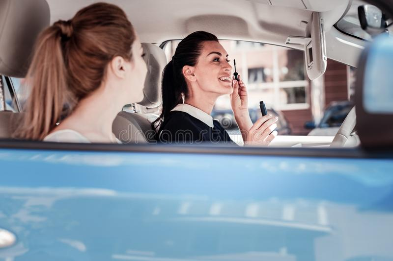 Pretty joyful woman looking in the mirror and sprucing. royalty free stock photography