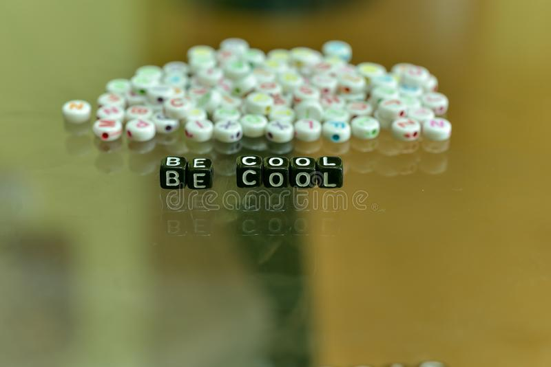 BE COOL  written with Acrylic Black cube with white Alphabet Beads on the Glass Background.  stock photos
